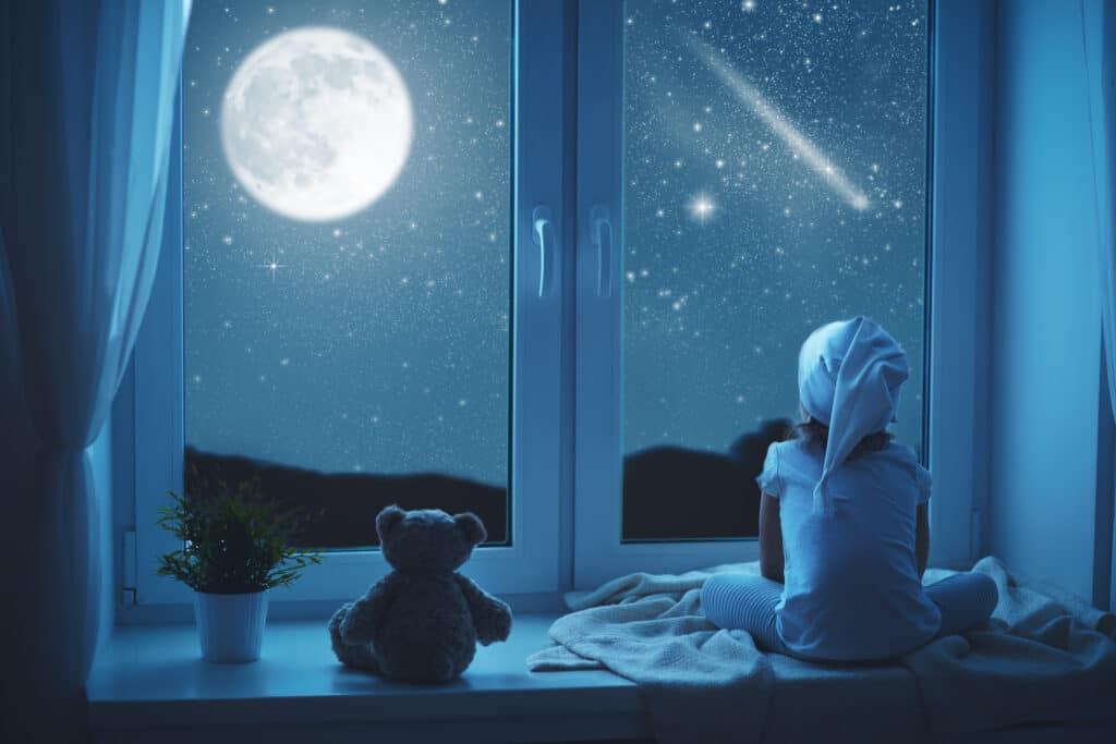 Ein Mädchen lauscht einer Gute-Nacht-Geschichte mit einem lieben Bär und schaut in die Sterne am Himmel