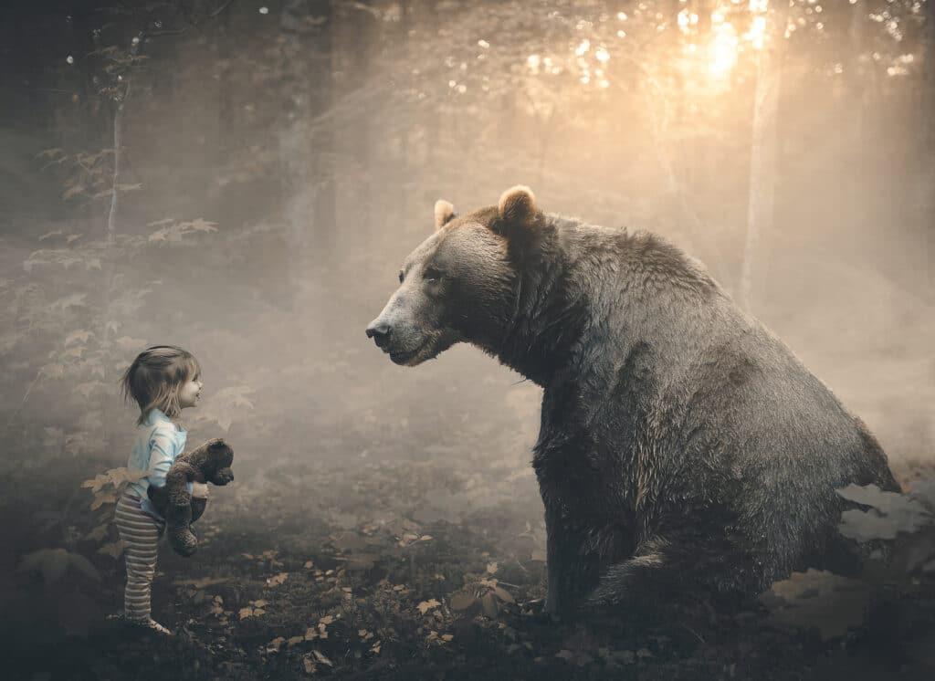 Ein Mädchen mit einem lieben Bär im Arm trifft einen echten Bären im Wald.
