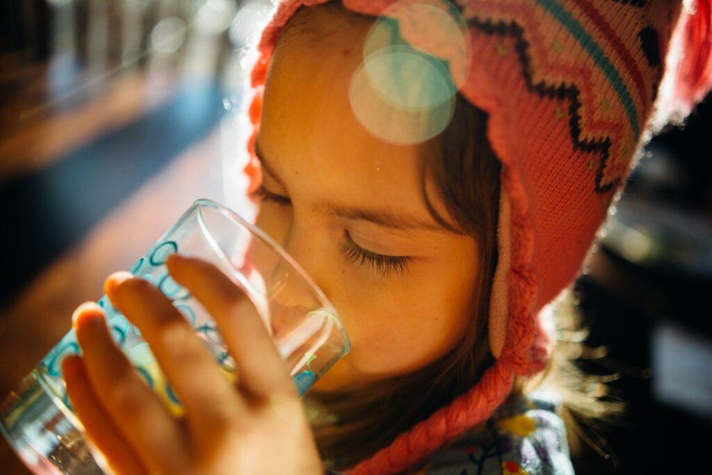An heißen Sommertagen sollten Kinder viel Wasser trinken, damit sie nicht dehydrieren.